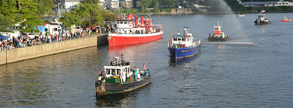 A group of boats passing a large gathering of people inet to the Erie Canalway